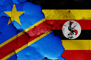 flags of DR Congo and Uganda painted on cracked wall
