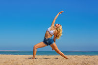 Young blonde woman training yoga on beach