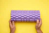 two male hands hold purple massage roll for back and body