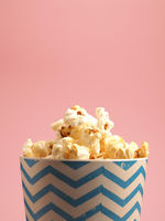 Fresh popcorn on a pink background