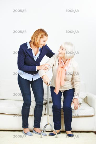 Krankenpflege hilft alter Frau beim Aufstehen