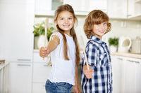 Zwei Kinder halten Kochlöffel in der Hand