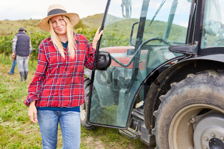 Frau als Erntehelfer am Traktor im Weinberg