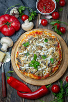Homemade pizza with tomatoes, mushrooms and green basil.