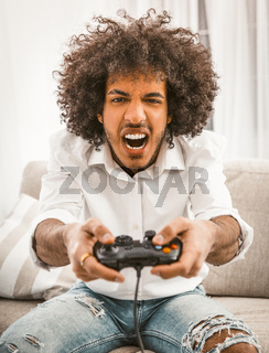 Screaming gamer shoots or attacks in computer game. The concept of emotions. Young Arab playing computer game sitting at sofa in home interior