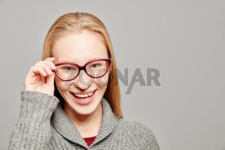 Blonde Frau mit Hand an Brille