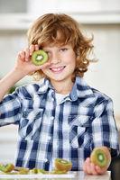 Junge zeigt Kiwi in Küche
