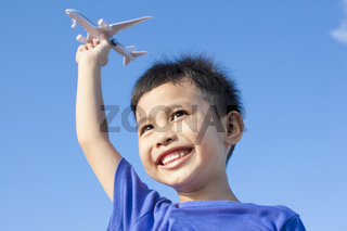 happy boy playing a airplane toy with blue sky background