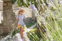 Beautiful blonde young female traveler wearing straw sun hat sightseeing and enjoying summer vacation in an old traditional village on Mediterranean cost