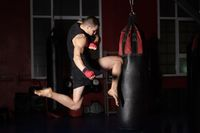 Kickboxing fighter Performing Jumping Air Kicks with Knee on Punch Bag. Caucasian Man Practicing Martial Arts Training at Urban Gym.