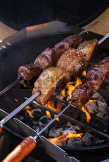 Barbecue dry aged wagyu picanha skewer preparing with salt on an open fire kettle grill