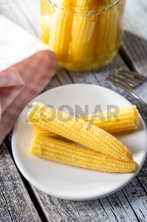 Pickled young baby corn cobs on plate.