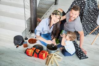 Glückliche Eltern spielen Camping und Zelten zu Hause