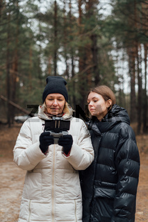Caucasian woman with adult daughter flying aerial drone in autumn forest.