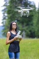 Teenage girl controlling drone with remote control in summer