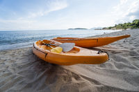 Two colorful orange kayaks on a sandy beach ready for paddlers in sunny day. Several orange recreational boats on the sand. Active tourism and water recreation.