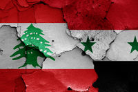 flags of Lebanon and Syria painted on cracked wall