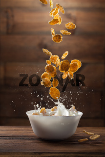 Falling corn flakes with milk splash on wood