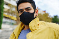 Young stylish man in yellow jacket in black protective mask poses outdoor.