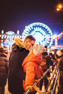couple hugging in Saint Valentine's Day. Young romantic pair having fun outdoors in winter. St. Valentines Day at city ice rink. New Year holidays. active date ice skating on ice arena on Christmas