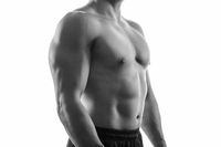 Young muscular shirtless man with beard, monochrome,  isolated on white background, side. Workout, fitness, diet concept.