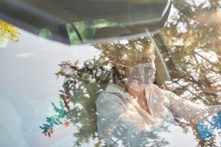 Blick auf Seniorin mit Mundschutz wegen Coronavirus am Steuer ihres Autos