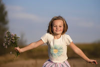 Happy little girl in the meadow with a bouquet of flowers. Child on a beautiful summer field.