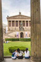 asian tourists taking a break in the gardens of alte nationalgalerie, old national gallery