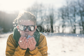 Handsome young man blowing snowflakes at sunny winter day