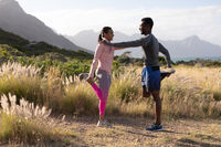 Fit african american couple in sportswear stretching in tall grass