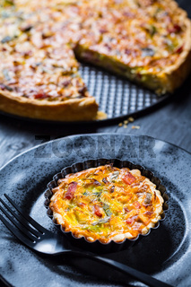 Quiche Lorraine - traditional French tart with pastry crust filled with bacon and leek