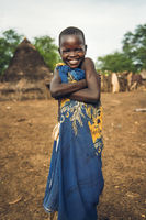 TOPOSA TRIBE, SOUTH SUDAN - MARCH 12, 2020: Happy kid wrapped in colorful cloth smiling for camera and crossing arms while living in Toposa Tribe village in South Sudan, Africa