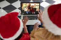 Rear view of woman and daughter in santa hats waving while having a videocall with woman and daughte
