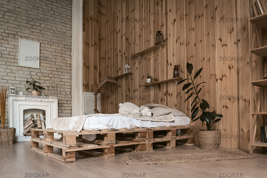 Cozy bedroom interior with white fireplace. Walls with wooden panels and bricks