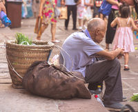 Tired chinese old man sitting on a pavement