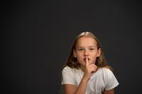 Keep quiet 8,10 years old girl holding her finger on her mouth telling everyone to keep silence wearing white t shirt smiling at the camera isolated on dark grey or black background. Copy space