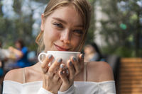 Pretty young blond woman with coffe cup in cafe smile and laugh.