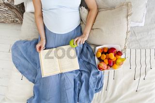 Positive pregnant woman eating fruits on bed