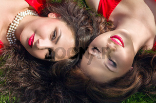 Two young beautiful women lying on the grass