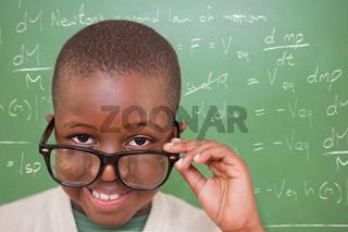 Composite image of cute pupil tilting glasses