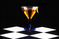 Cocktail in a blue stemmed glass on black and white checkerboard tile