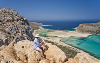 Woman artist sits on the stones and paints a picture of Tigani cape and Balos lagoon with sandy beach. Crete, Greece.