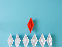 Leadership or Teamwork business concept with paper boat on a blue paper background
