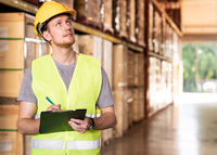 Portrait white caucasian worker with archboard in distribution warehouse