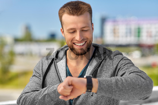 happy man with fitness tracker in city