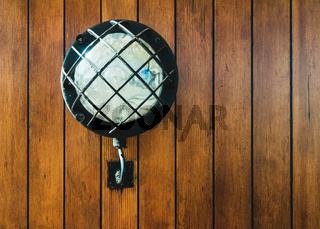 Vintage lamp on old sailboat wooden wall