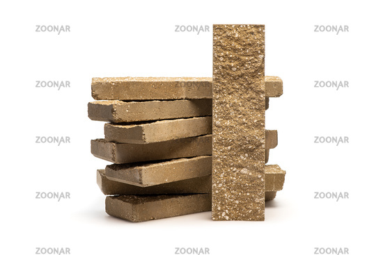 Decorative facing bricks for fence or wall on white background. Brick with rocky relief surface