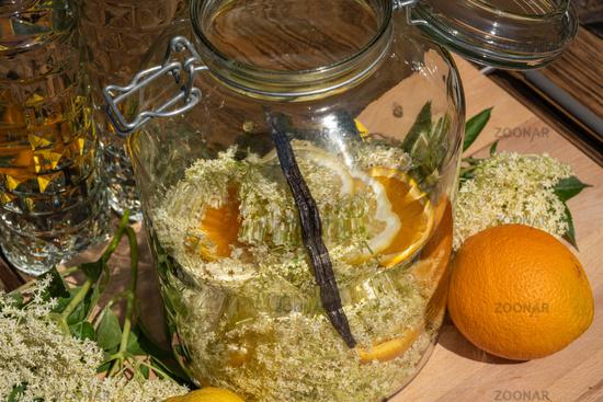 Elderberry blossoms and orange and lemon slices in a large preserving jar