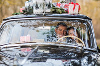 Couple in vintage car with presents on roof