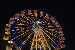 Ferris wheel with lights backlighting the night sky